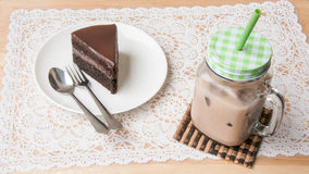Ice coffee and chocolate cake on table. Ice coffee and chocolate cake on wooden table Stock Image