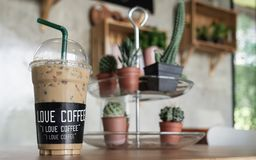 Ice coffee with I love coffee label in a lovely coffee shop green plant decoration. royalty free stock photography