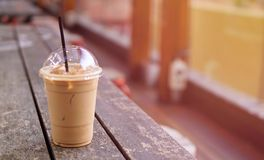 Ice coffee latte in takeaway cup on wood table. Takeaway ice lat stock image