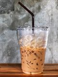 Ice coffee in plastic cup and brown tube. On the wooden table with cement wall, relaxing and freshy, Vintage style and Natural light royalty free stock image