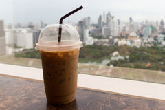 Ice coffee in plastic glass on the table with park and city in background, relax before starting hardwork in a day Royalty Free Stock Image