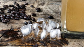 Ice coffee put on a wood table with dark roasted coffee beans. And flowers Royalty Free Stock Photos