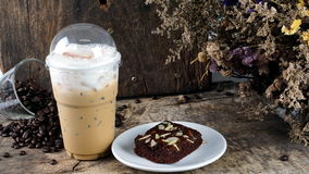 Ice coffee put on a wood table with dark roasted coffee beans. And flowers Royalty Free Stock Image