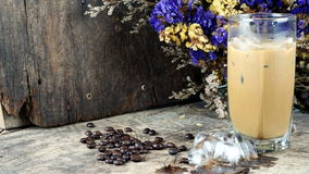 Ice coffee put on a wood table with dark roasted coffee beans. And flowers Royalty Free Stock Photo