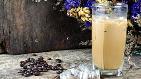 Ice coffee put on a wood table with dark roasted coffee beans. Ice coffee of latte, cappuccino or espresso coffee with milk put on a wood table with dark roasted Royalty Free Stock Photos