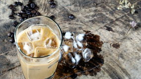 Ice coffee put on a wood table with dark roasted coffee beans. Ice coffee of latte, cappuccino or espresso coffee with milk put on a wood table with dark roasted Royalty Free Stock Photo