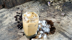 Ice coffee put on a wood table with dark roasted coffee beans. Ice coffee of latte, cappuccino or espresso coffee with milk put on a wood table with dark roasted Royalty Free Stock Image