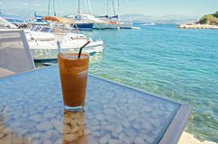 Ice coffee on a table sea in background. Ice coffee on a table with a view of the sea and harbor Royalty Free Stock Image