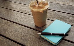 Ice coffee in takeaway cup with notebook and pen on the side. Bo stock photo
