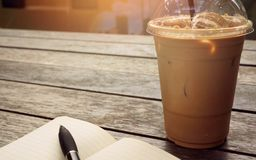 Ice coffee in takeaway cup with notebook and pen on the side. Bo royalty free stock photo