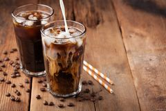 Ice coffee in a tall glass with cream poured over and coffee beans on a old rustic wooden table. Cold summer drink on a dark woode Royalty Free Stock Image