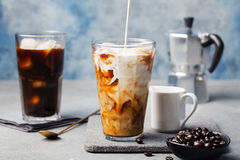 Ice coffee in a tall glass with cream poured over and coffee beans Stock Photos