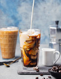 Ice coffee in a tall glass with cream poured over and coffee beans on a grey stone background Royalty Free Stock Photography
