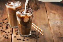 Ice coffee in a tall glass with cream poured over and coffee beans on a old rustic wooden table. Cold summer drink on a Royalty Free Stock Images