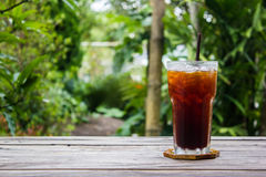 Ice coffee on wood table with green nature background. Copy space.  stock photos