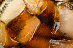 Ice in coke glass background. Ice cubes floating in a glass of coke Stock Photos