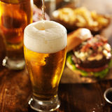 Ice cold beer pouring into glass. With burgers at restaurant table Royalty Free Stock Photography