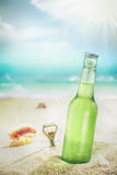 Ice cold bottle of lager or soda on a beach Royalty Free Stock Photo