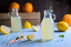Ice cold citrus lemonade on wooden table. On natural background Stock Images