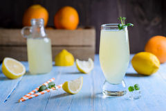 Ice cold citrus lemonade on wooden table. On natural background Royalty Free Stock Photography