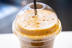 Ice cold coffee froth in a plastic cup. Ice cold coffee froth in a disposable plastic cup with straw stock images