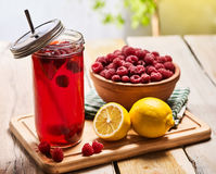Ice cold drink jar glass with raspberry and lemon cocktail . Stock Photography