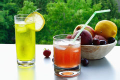 Ice-cold fruit lemonade in glasses. Two glasses of ice-cold fruit lemonade and fresh fruits in a wooden bowl on the table Stock Photography