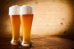 Ice cold glasses of frothy larger or wheat draft beer. Two ice cold glasses of frothy larger or wheat draft beer on a rustic bar counter with side vignette and royalty free stock photo