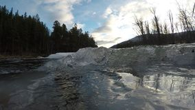 Ice cold mountain creek water ice buildup on big river entrance in the northern winter. Slow motion stock video footage