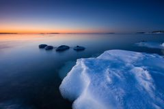 Ice and cold water. This is photographed after sunrise in the coast of Uutela, Helsinki. There is  ice in foreground and open water in background Stock Photo