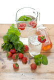 Ice cold water. Fresh water with ice cubes, mint, strawberries and lemon slice Stock Image