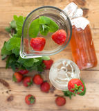 Ice cold water. Fresh water with ice cubes, mint, strawberries and lemon slice Royalty Free Stock Images