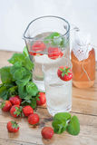 Ice cold water. Fresh water with ice cubes, mint, strawberries and lemon slice Stock Photos