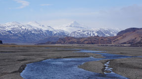 Ice and colourfull mountains on Iceland. Glaciers and rhyoliet mountains near Vatnajökull on Iceland in spring when the snow is melting into the riverbed royalty free stock photography