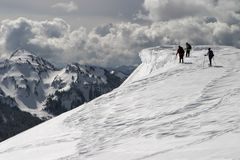 Ice Cornice. Three climbers nearing the edge of a dangerous cornice on Mt. Rainier. Storm clouds in the distance provide drama to the scene Royalty Free Stock Image