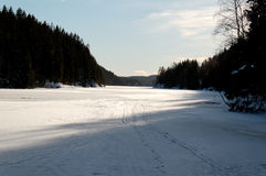 Ice-Covered Lake. Surface of Elvåga lake near Oslo, Norway is covered by ice with ski tracks and occasional weak points on it. Elvåga dam is visible in the Royalty Free Stock Images