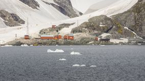 Ice covered mountain and people walking near the camp in Antarctica stock photo