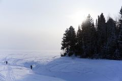The mouth of the winter river. Ice-covered mouth of a winter river flowing into a lake, in a frosty haze, with a high shore and people walking on ice Stock Photos