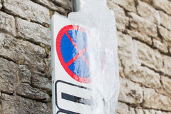 Ice-covered no stopping road sign over wall Stock Photos