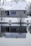 Ice covered pond - back of the house reflecter in freezing water Stock Image