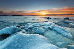 Ice covered rocks. On the beach with colorful sunrise Royalty Free Stock Photo
