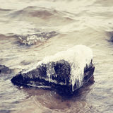 Ice-covered stone in water Stock Photos