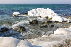 Ice covered stones on  seashore Royalty Free Stock Photos
