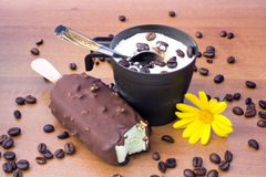 Ice Cream. Food & Drinks - Desserts - Cup with vanilla ice cream and bited ice cream bar on wood table, decorated with coffee grains and yellow daisy Stock Photos