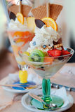 Ice-cream. Tasty ice-cream with tropical fruits, waffles and chocolate on the table in cafe Royalty Free Stock Photo