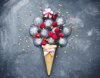 Ice cream association concept frozen berries and ice cream sugar sprinkles. Ice cream association concept - waffle cone filled with ice, frozen berries and ice royalty free stock photo