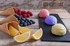 Ice cream assorted balls with lemon raspberry bilberry on a stone surface with pieces of fruit. Delicious fresh fruits ice cream. royalty free stock photos