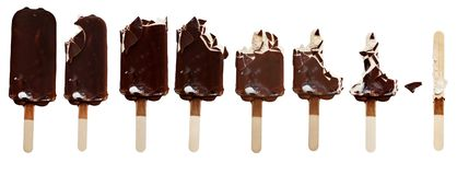 Ice Cream Bars Being Eaten. Progression of chocolate covered vanilla ice cream bars on a wooden stick with bites taken out. Isolated over a white background Royalty Free Stock Photography