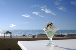 Ice-cream on a beach. Portion of ice-cream against sea coast and sunset Stock Images