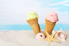 Ice cream on the beach. Two ice cream cones and seashells in the sand on the beach Royalty Free Stock Images
